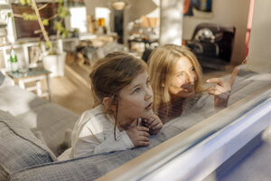 Mature woman and girl at home on couch looking out of window - JOSF00895