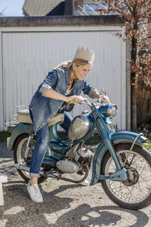 Happy woman on vintage motorcycle wearing a crown - JOSF00901