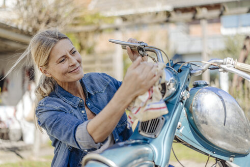 Smiling woman cleaning vintage motorcycle - JOSF00904