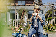 Woman on vintage motorcycle enjoying a coffee break - JOSF00907