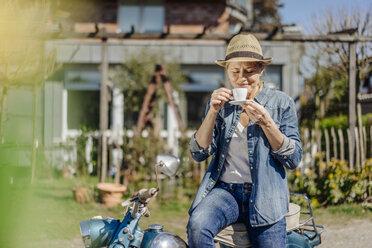 Woman on vintage motorcycle enjoying a coffee break - JOSF00907
