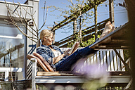 Smiling woman reading book on garden bench - JOSF00910