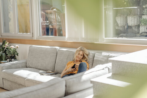 Woman at home on couch using cell phone - JOSF00913