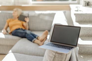 Laptop on couch with woman in background - JOSF00916