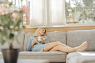 Woman at home lying on couch with cup of coffee - JOSF00919