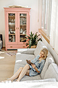 Woman at home on couch with tablet - JOSF00922