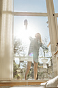 Woman cleaning the window in sunshine - JOSF00928