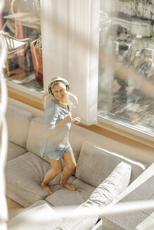 Happy woman at home wearing headphones dancing on the couch - JOSF00931