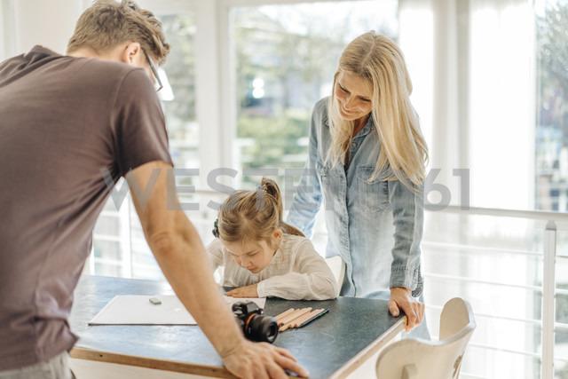 Mature woman and man looking at girl drawing at home - JOSF00937