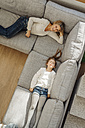 Happy mature woman and girl at home lying on couch - JOSF00940
