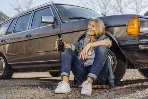 Woman sitting at car drinking a beer - JOSF00946