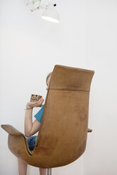 Child sitting on armchair holding box with painted mouse - PSTF00009