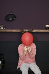 Girl in kitchen hiding behind balloon - PSTF00018