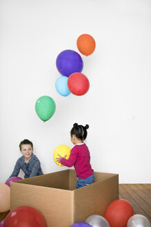 Two kids playing with balloon and cardboard box - PSTF00024