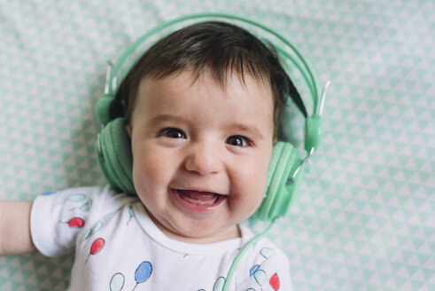 Portrait of laughing baby girl with headphones - GEMF01612