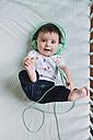Portrait of baby girl lying in crib listening music with headphones - GEMF01615