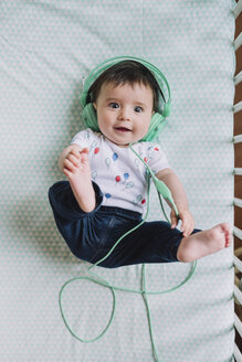 Portrait of baby girl lying in crib listening music with headphones - GEMF01615