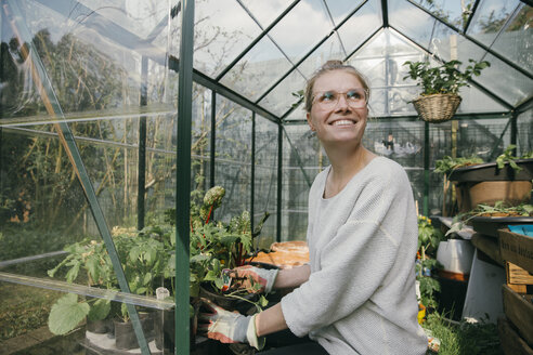 Portrait of happy young woman in her greenhouse - MFF03487