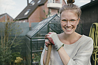 Portrait of smiling young woman with rake in the garden - MFF03493