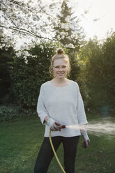 Portrait of young woman sprinkling lawn in the garden - MFF03502