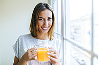 Portrait of smiling young woman with glass of orange juice - KIJF01476