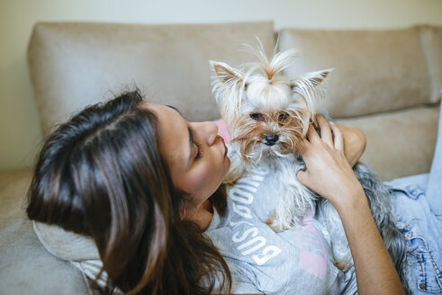 Woman lying on couch with her Yorkshire Terrier - KIJF01482