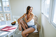 Young woman sitting on basket-chair at home looking through window - KIJF01494