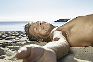 Mature man relaxing on sandy beach - PDF01228