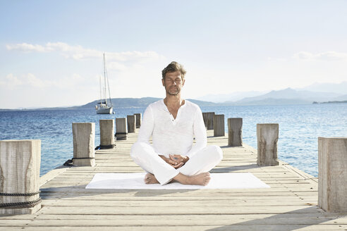 Mature man doing yoga exercise on jetty - PDF01231