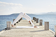 Mature man doing yoga exercise on jetty - PDF01234