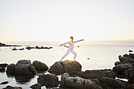 Mature man doing yoga exercise on a rock at the sea - PDF01237