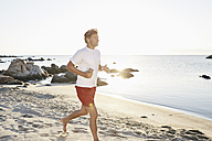Mature man jogging on the beach while listening music with smartphone and earphones - PDF01240