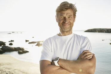 Portrait of smiling mature man with smartwatch and earphones on the beach - PDF01243