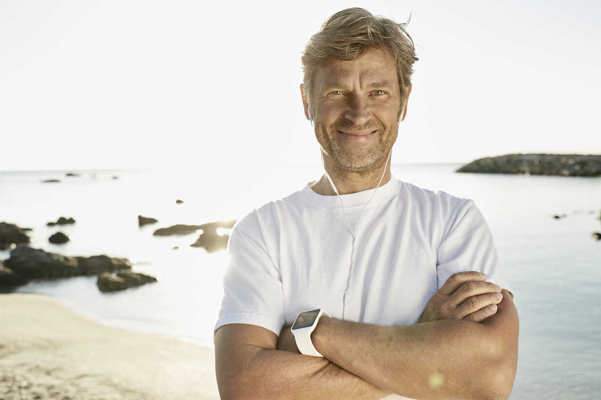 Portrait of smiling mature man with smartwatch and earphones on the beach - PDF01243 - Philipp Dimitri/Westend61
