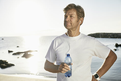 Portrait of mature man with smartwatch and earphones drinking water after jogging on the beach - PDF01249