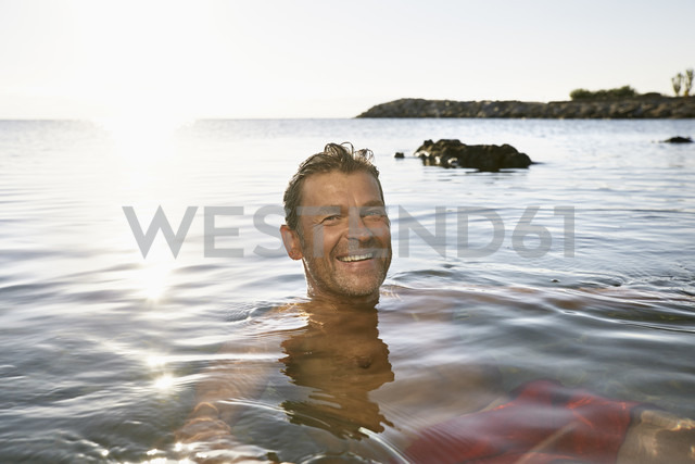 Portrait of smiling man bathing in the sea - PDF01252