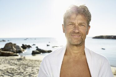 Portrait of smiling man with towel in front of the sea - PDF01255