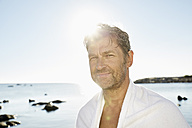Portrait of smiling man with towel in front of the sea - PDF01258