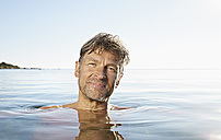Portrait of smiling man bathing in the sea - PDF01261