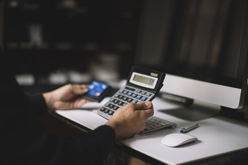 Man using calculator and credit card at desk, partial view - JPF00196