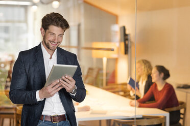 Young businessman in office using digital tablet, with coworkers in background - PESF00565