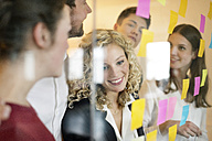 Business people discussing in front of glass screen with sticky notes - PESF00577