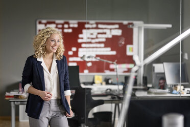Dynamic businesswoman standing in office, smiling - PESF00580