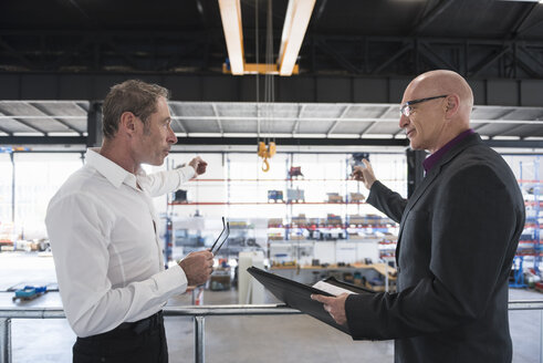 Two businessmen with clipboard talking on factory shop floor - DIGF02476