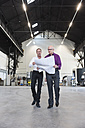 Two businessmen with plan walking in factory shop floor - DIGF02485