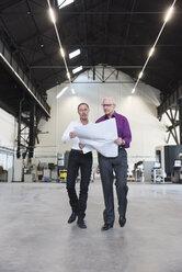 Two businessmen with plan walking in factory shop floor - DIGF02485