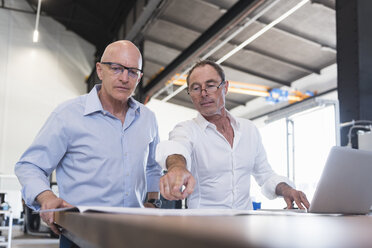 Two businessmen looking at plan on table in factory - DIGF02491