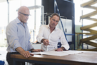 Two businessmen looking at plan on table in factory - DIGF02494