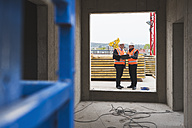 Two men wearing safety vests talking in building under construction - DIGF02509