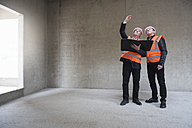 Two men wearing safety vests talking in building under construction - DIGF02512